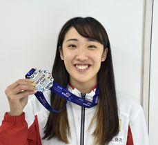 トランポリンのW杯から帰国し、獲得した銀メダルを手にする森ひかる=23日、成田空港