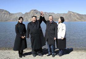 朝鮮半島最高峰の白頭山を訪問し、カルデラ湖「天池」でつないだ手を上げる北朝鮮の金正恩朝鮮労働党委員長(中央左)と韓国の文在寅大統領(同右)。夫人が同行した=20日(平壌写真共同取材団・共同)