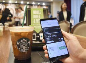 スマートフォンのスターバックスコーヒージャパンのアプリ画面と商品=25日午後、東京都千代田区