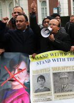オランダ・ハーグの国際司法裁判所前で、ミャンマーのアウン・サン・スー・チー国家顧問兼外相に反発するロヒンギャの支援者ら=10日(共同)
