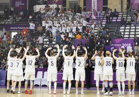 バスケットボール女子でインドネシアに勝利し、スタンドの応援団に向かって手を振る南北合同チーム「コリア」の選手=15日、ジャカルタ(共同)