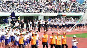開会式で力強い行進を見せる高校生たち=25日午前、宮崎市・KIRISHIMAハイビスカス陸上競技場