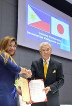 協定を結んだ「外国人・日系人サポートセンター」の新垣安男代表理事(右)=20日、マニラ(共同)