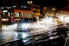 あびきの影響で冠水した道路=21日午後9時23分、長崎市宝町