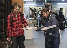 行方不明となった小倉美咲さんの情報提供を呼び掛けるチラシを配布する母とも子さん(右)=21日午後、山梨県大月市
