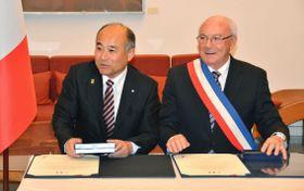 10日、フランス・パリで姉妹都市提携の調印式を行う熊本県相良村の徳田正臣村長(左)とサンバランタン村のルッソー村長(共同)