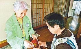訪問先の家庭でみそ汁の塩分濃度を測定する調査隊員