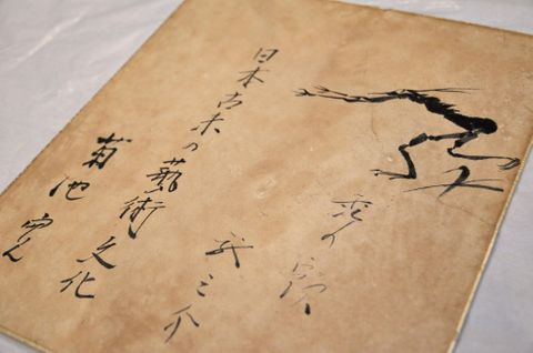 芥川龍之介と菊池寛が合作した色紙。右上に河童が描かれ、その下に芥川、左に菊池の署名が見える=25日、東京都北区の田端文士村記念館
