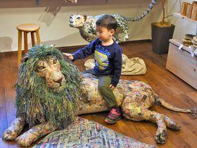 新聞紙を使って動物の作品。約2メートルのライオンの作品は人が乗ることもできる(京都市中京区・川端滝三郎商店)