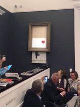 5日、ロンドンでの競売で路上芸術家バンクシーの作品が落札直後に細断される様子を写した動画(PIERRE KOUKJIAN提供、AP=共同)