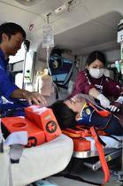 愛媛、広島両県合同訓練でドクターヘリ内で負傷者を初期治療する医療関係者ら=19日午後、同町岩城