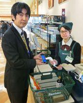 実験店舗のスーパーで電子レシートを受け取る様子=13日午後、東京都町田市