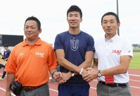 桐生祥秀選手(中央)と握手する、男子100メートル決勝でスターターを務めた福岡渉さん(左)ら=福井県営陸上競技場