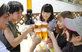 「さっぽろ大通ビアガーデン」でビールを手に乾杯する人たち=20日午後、札幌市