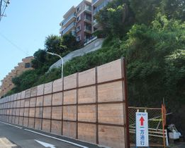 事故が起きた斜面はモルタルで吹き付けられて防護柵も置かれ、片側通行となっている=4日、逗子市池子