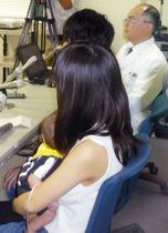 手術を受けた男児を抱いて記者会見する母親(手前)と、執刀した中京病院の桜井一心臓血管外科部長(右端)=13日午前、名古屋市
