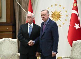 17日、トルコの首都アンカラで握手するエルドアン大統領(右)とペンス米副大統領(ゲッティ=共同)
