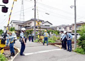 列車と衝突した踏切を調べる小松島署員ら=28日午前9時40分ごろ、小松島市横須町