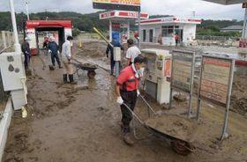 ガソリンスタンドの営業再開に向け、一輪車で泥を運び出す従業員ら=15日午後、常陸大宮市野口、吉田雅宏撮影