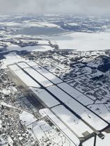 米軍のF16戦闘機が燃料タンクを投棄した雪に覆われた小川原湖(奥)。手前は三沢基地=20日午後0時26分、青森県三沢市(共同通信社機から)
