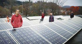 学校屋上に中高生が作ったソーラーパネルを取材した場面。発電して電力を売り、環境保全と経済を学ぶ(シネマテークたかさき提供)