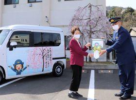 桜が描かれた寄贈車両の前で、鍵の模型を手渡す石川さん(左)=綾部市宮代町・綾部署