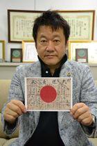 日章旗の写真を手に情報提供を呼び掛ける伊藤博文館長=6日、沖縄タイムス社