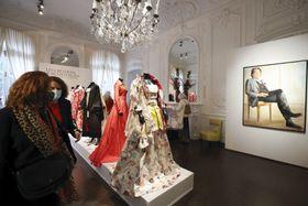 パリの競売会社アールキュリアルで、オンラインオークションにかけられた高田賢三さん創作のドレスなどを見る女性ら=7日(共同)