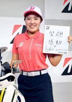 「笑顔 感動」と書かれた色紙を手に、笑みを浮かべる古江彩佳=29日午前、東京都内