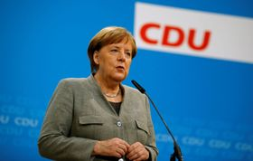 21日、ドイツ・ベルリンで記者団に話すメルケル首相(ロイター=共同)