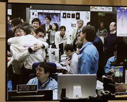 探査機はやぶさ2から小惑星着陸後の上昇行動の信号を受信し、喜ぶ管制室のJAXA職員ら=22日午前7時51分、相模原市
