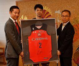 松戸市長(右)に今季の成績を報告し、富樫選手のユニホームを寄贈する千葉ジェッツふなばしの島田代表(左)と石井選手=13日、船橋市役所