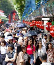 東京・浅草の仲見世商店街で日傘を差す観光客ら=17日午後