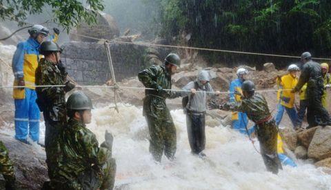 自衛隊員らのサポートで濁流の中を渡る登山者=屋久島町の県道屋久島公園安房線