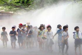 噴射される霧を浴びる子どもたち=23日午前、神戸市立王子動物園