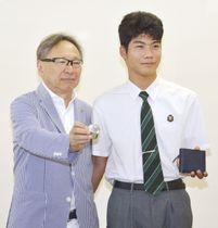 贈られた文鎮を手にする猪野屋博さん(左)と、財布を手にする崎元颯馬さん=21日午後、那覇市