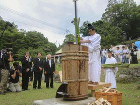 葉を落とした大麻の茎を熱湯にくぐらせる「初蒸式」=15日、徳島県美馬市木屋平