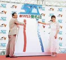 東名高速道路の全線開通50周年記念モニュメントに色を塗る吉田沙保里さん(右)ら=26日午後、小山町の足柄サービスエリア