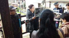 山口彊さんの証言を朗読する原田小鈴さん(中央)=長崎市水の浦町