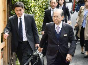 捜査員と自宅に向かうジャパンライフの山口隆祥元会長(右)=25日午前、東京都文京区