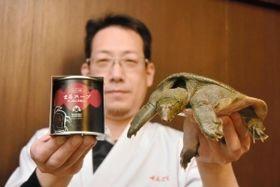 生きたスッポンを手に缶詰をPRする立谷利津男さん=姫路市飾磨区野田町