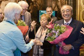 「ショーン・マクブライド平和賞」の授賞式でメダルを受け取る「オール沖縄会議」の高里鈴代共同代表(中央)と、花束を受け取る安次富浩さん(右)=11月24日、スペイン・バルセロナ