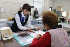 チェックシートを使い、住民に説明する行員=雲仙市、親和銀行千々石支店