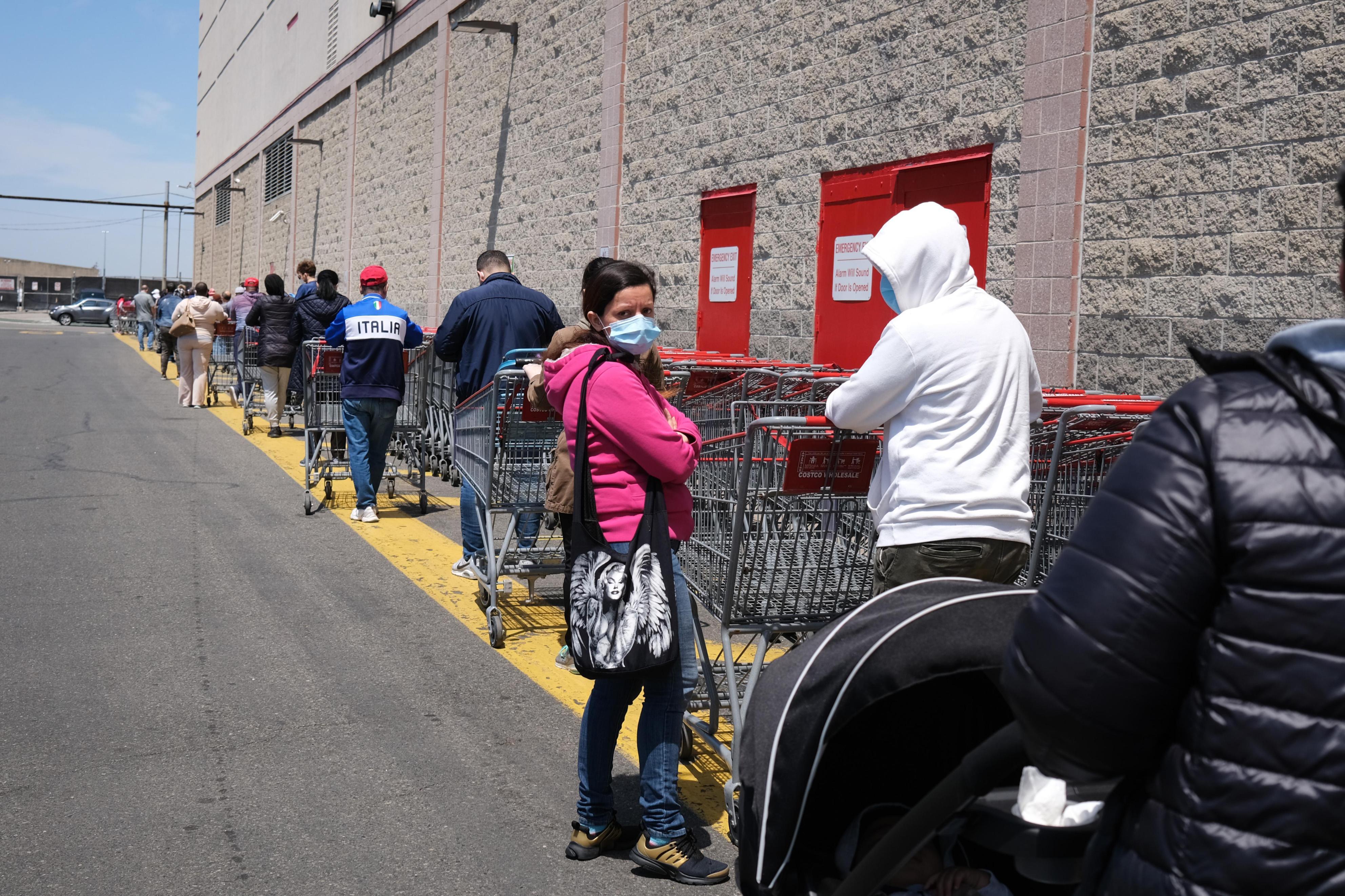 コストコの外で一列になって待つ人々=14日、ニューヨーク(ゲッティ=共同)