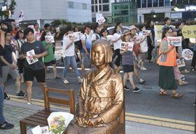 17日、韓国・釜山の日本総領事館前に設置された元従軍慰安婦を象徴する少女像のそばでデモ行進する市民ら(共同)