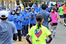 ランナーに声援を送るボランティア=10日午後、宮崎市青島