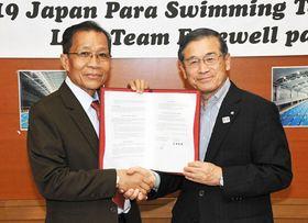 覚書を締結し、握手を交わす菅野村長(右)とサイサナソングカム副会長