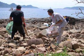 岩場の漂着ごみを拾い集める平戸市職員ら=平戸市、中江ノ島