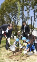 皇陛下の在位30年を記念しシダレザクラの苗を植える西予市の管家一夫市長(左)と保育園児ら