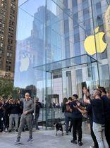 大規模な改装工事を行い開店した旗艦店の入り口で手を振る米アップルのティム・クックCEO(左手前)=20日、ニューヨーク(共同)